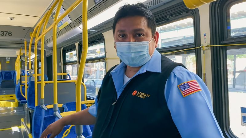 A man in a bus-driver's uniform stands on an empty bus, wearing a paper mask.