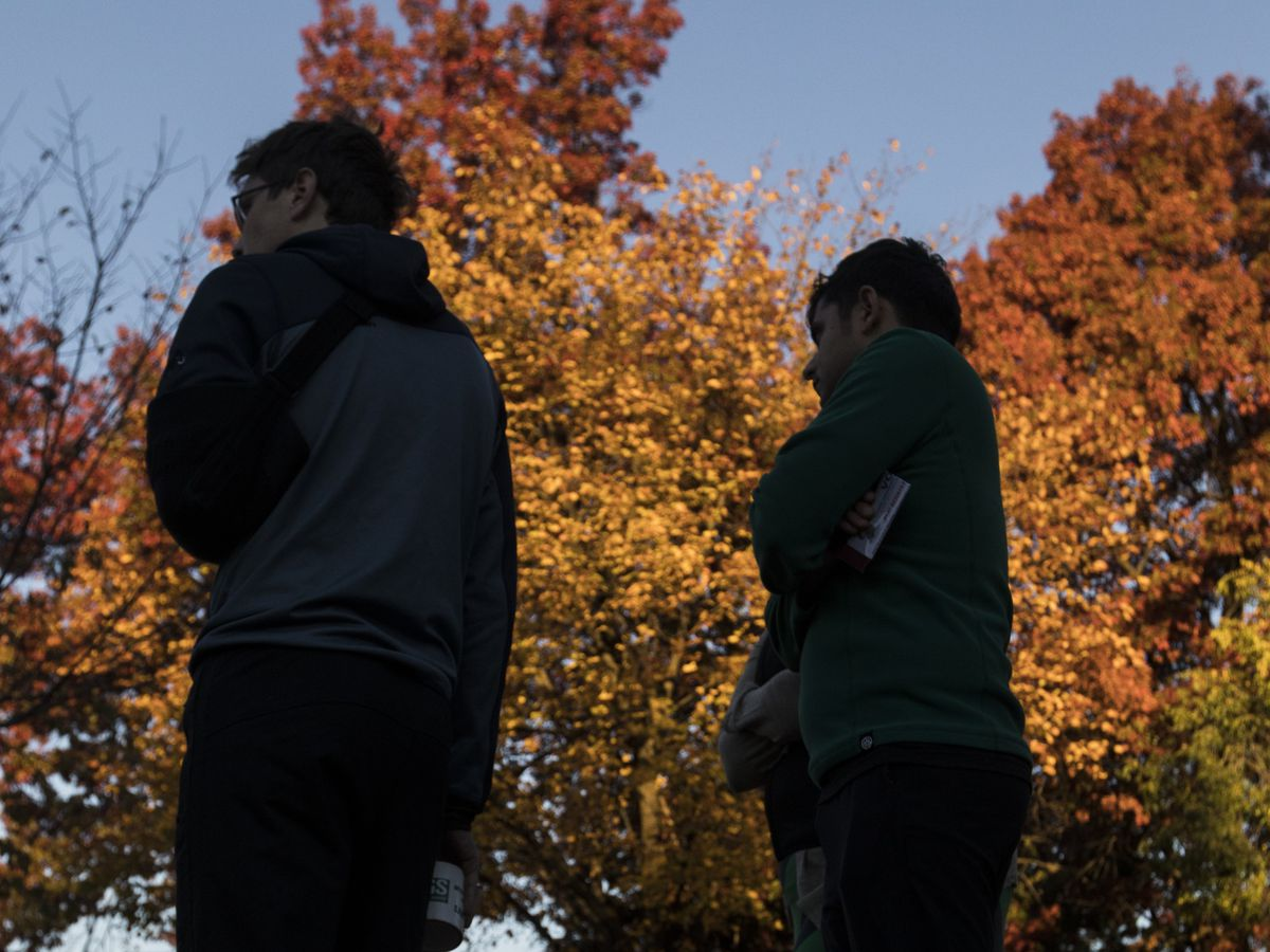Two men wait to vote beneath multicolor trees during the fall.