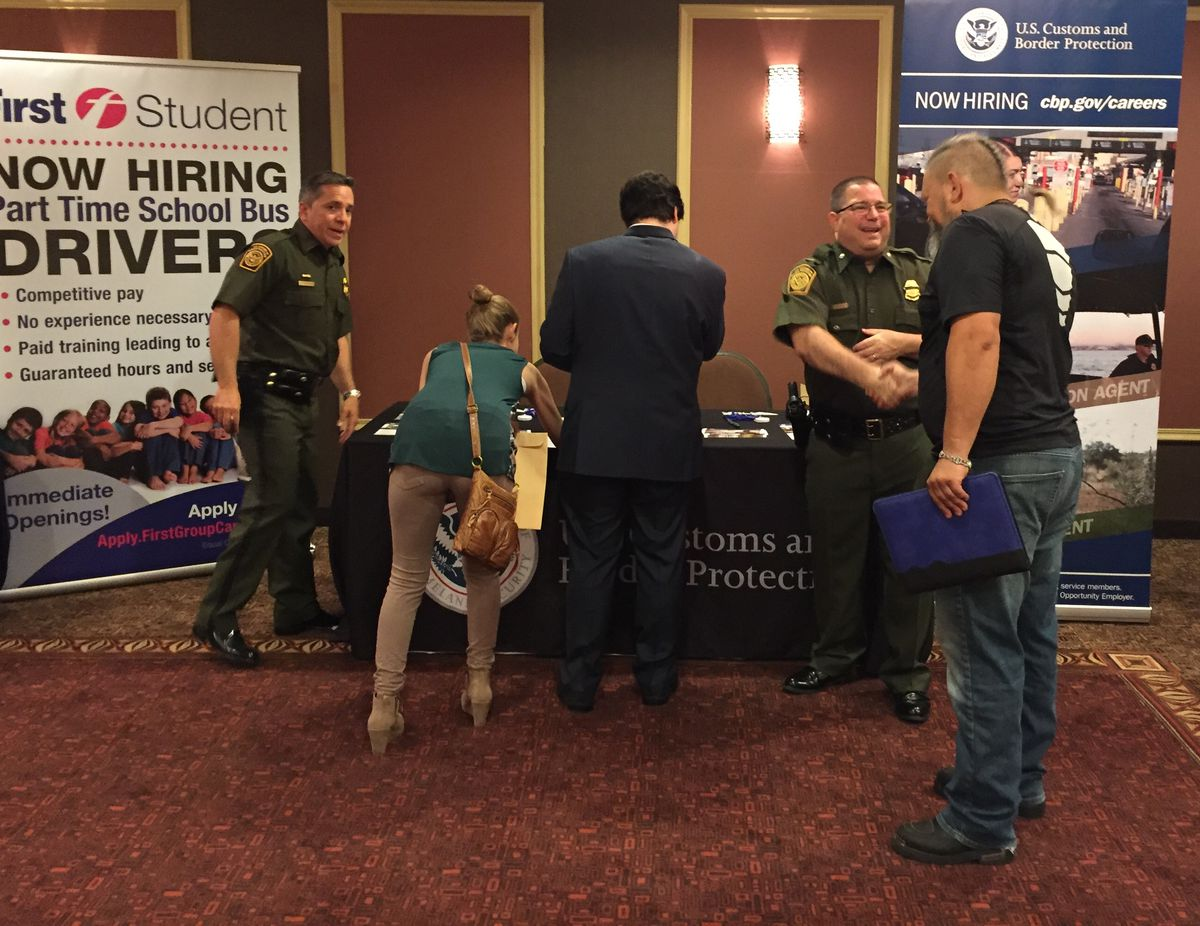 U.S. Border Patrol agents Orlando Ruiz (left) and Bill Burke, shaking hands, were at the Holiday Inn Express in Palatine on Thursday talking to job seekers interested in protecting our country's southern border.   Neil Steinberg/Sun-Times