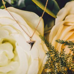 """Catbird rose thorn necklace with pavé diamonds, <a href=""""https://catbirdnyc.com/shop/product.php?productid=19797&cat=105&page=1"""">$524</a>; <a href=""""https://www.sprouthome.com/"""">Sprout Home</a> arrangement (call 718-388-4440 for info)"""