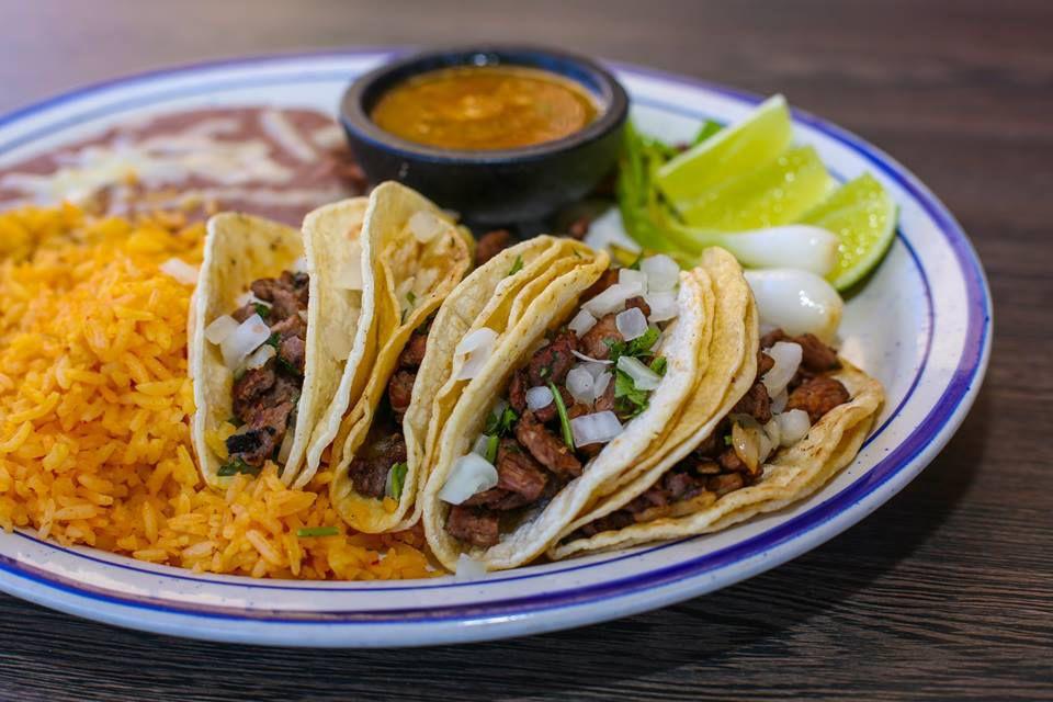 Tacos with rice, limes, and salsa at Juan's Flaming Fajitas & Cantina.
