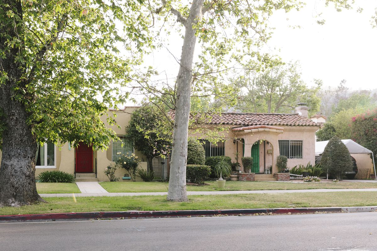 Two Spanish-style home with tiled roofs and peachy stucco facades on a suburban street lined with maple trees.