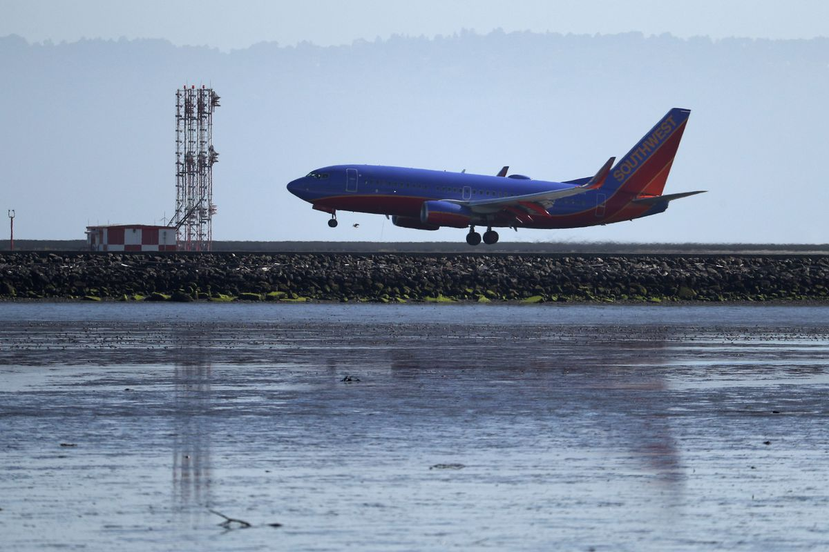 A Boeing 737 plane on the runway at San Francisco International Airport, seen in profile.