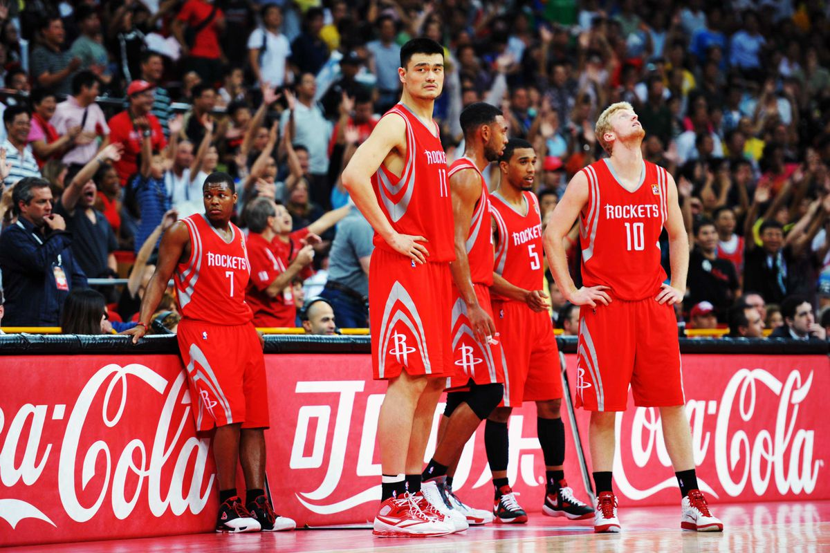 Yao Ming of the Houston Rockets standing on the court with four other players during a basketball game.