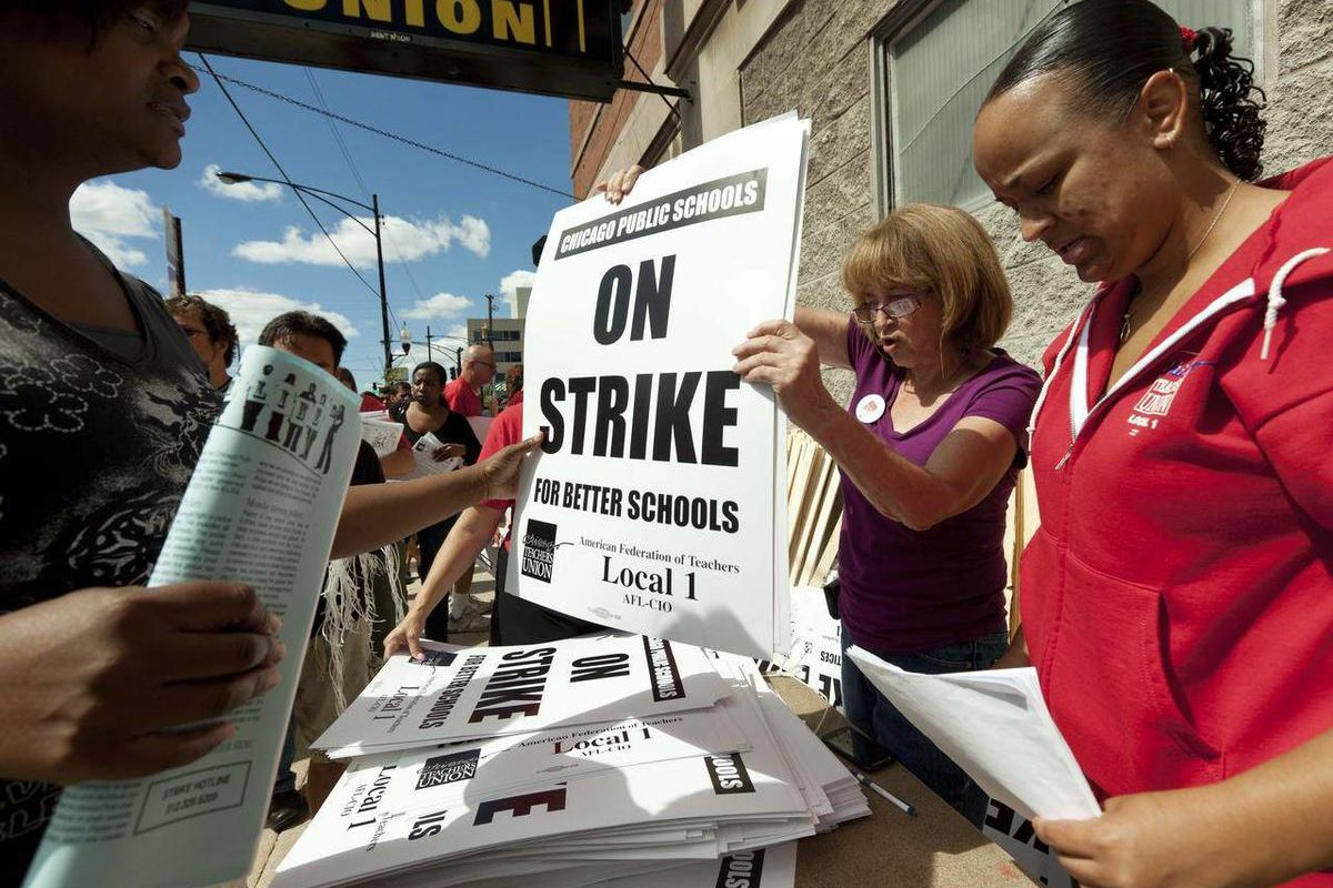 FILE - In this Saturday, Sept. 8, 2012 file photo, members of the Chicago Teachers Union distribute strike signage at the Chicago Teachers Union strike headquarters in Chicago. The Chicago Teachers Union announced Sunday night that its 25,000 members will
