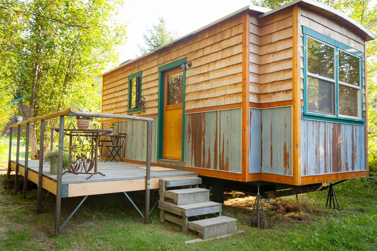 The exterior of a tiny home in Idaho. There is a wooden facade and a wooden deck with a table and chairs.