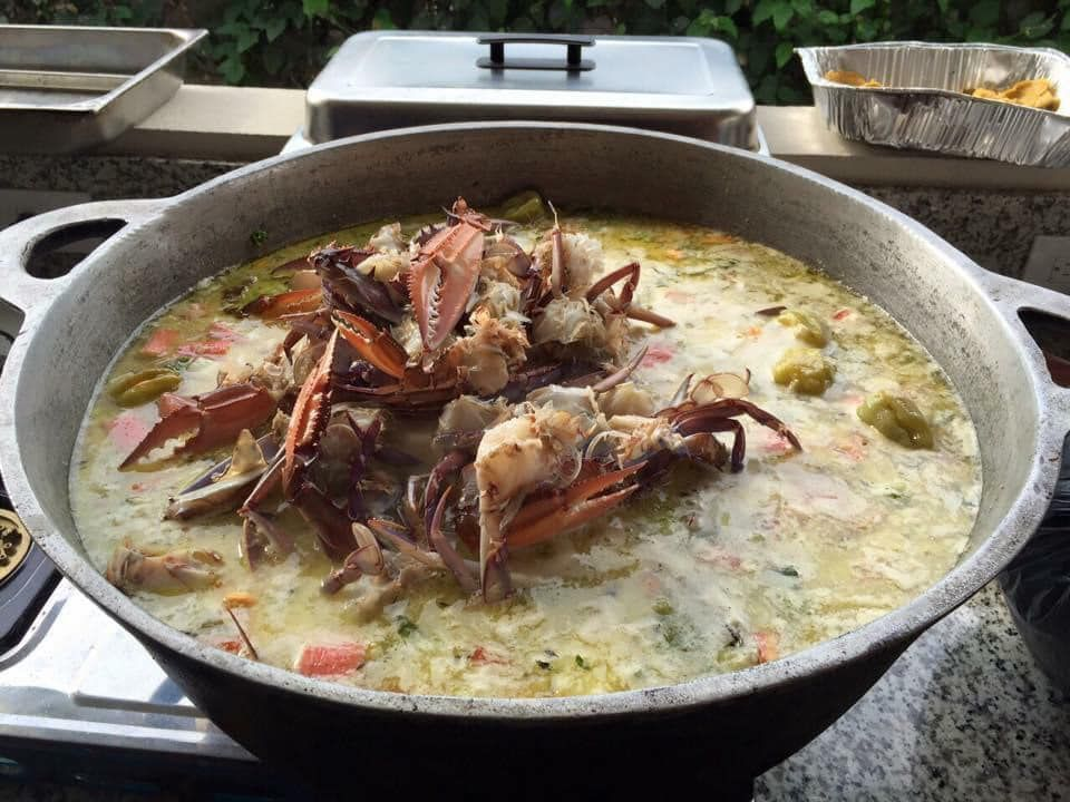 A large full stew pot with cooked crabs piled above the surface