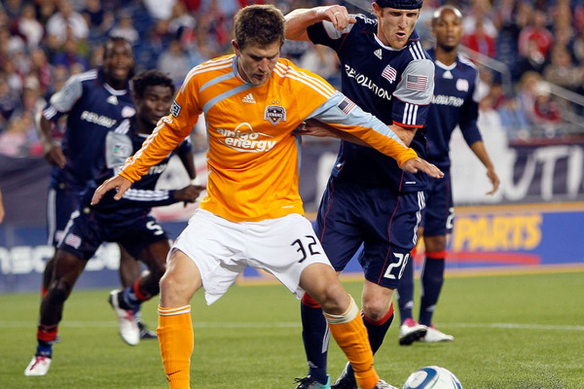 FOXBORO MA - AUGUST 14: Pat Phelan # 28 of the New England Revolution keeps Bobby Boswell # 32 of the Houston Dynamo away from the Revolution's net at Gillette Stadium on August 14 2010 in Foxboro Massachusetts. (Photo by Jim Rogash/Getty Images)
