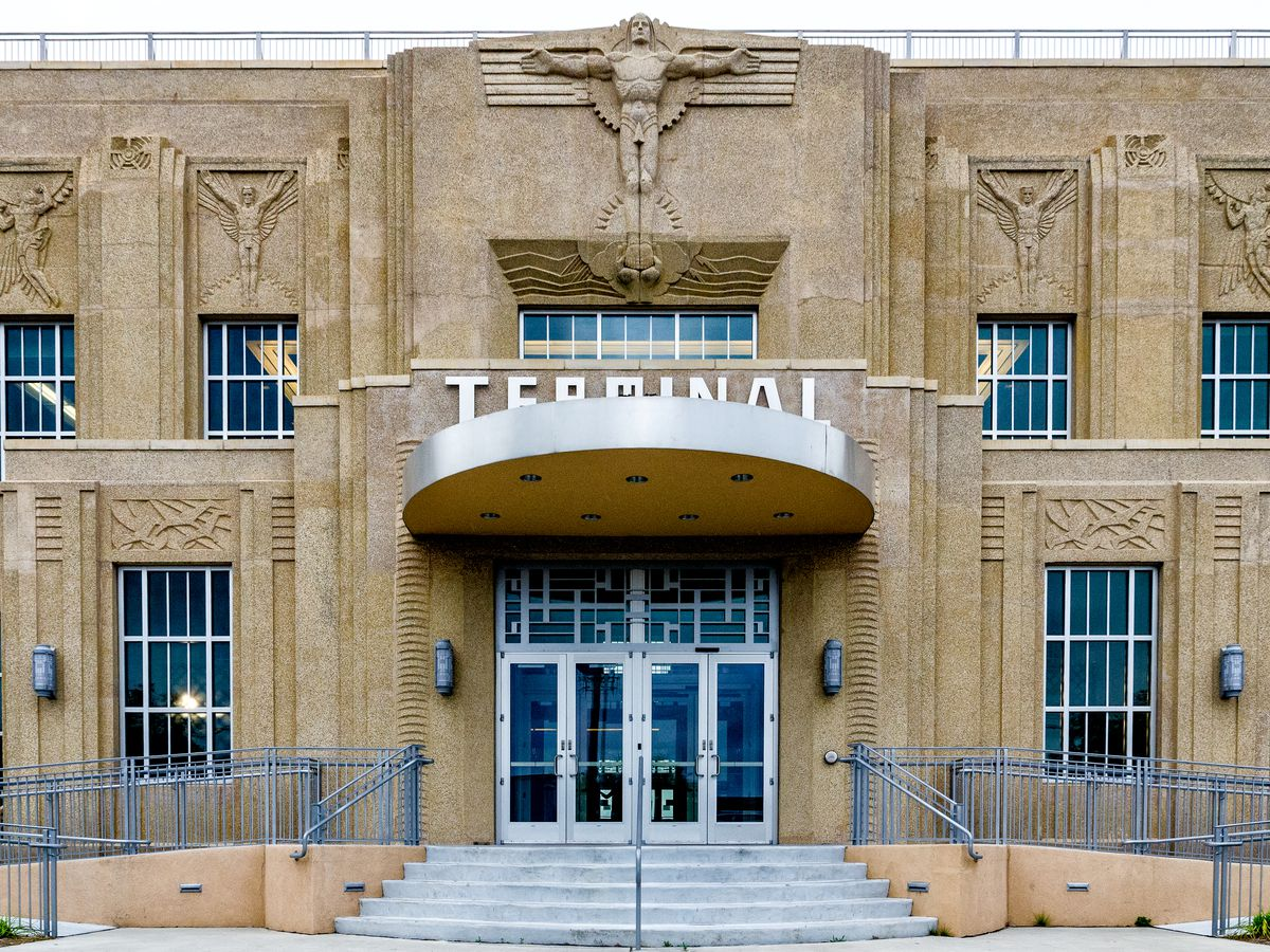 The exterior of the New Orleans Lakefront Airport. The facade is tan with decorative sculptures over each window. There is a sign on top of the awning over the entrance that reads: terminal.