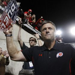Utah Head Coach Kyle Whittingham raises the Deseret Dual trophy up for fans as he leaves the field after his team defeated BYU 54-10 Saturday, Sept. 17, 2011