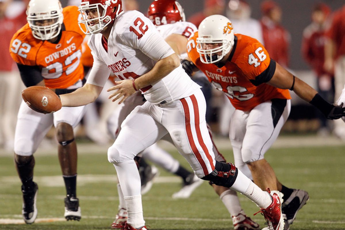 STILLWATER OK - NOVEMBER 27:  Quarterback Landry Jones #12 of the Oklahoma Sooners hands the ball off against the Oklahoma State Cowboys at Boone Pickens Stadium on November 27 2010 in Stillwater Oklahoma.  (Photo by Tom Pennington/Getty Images)