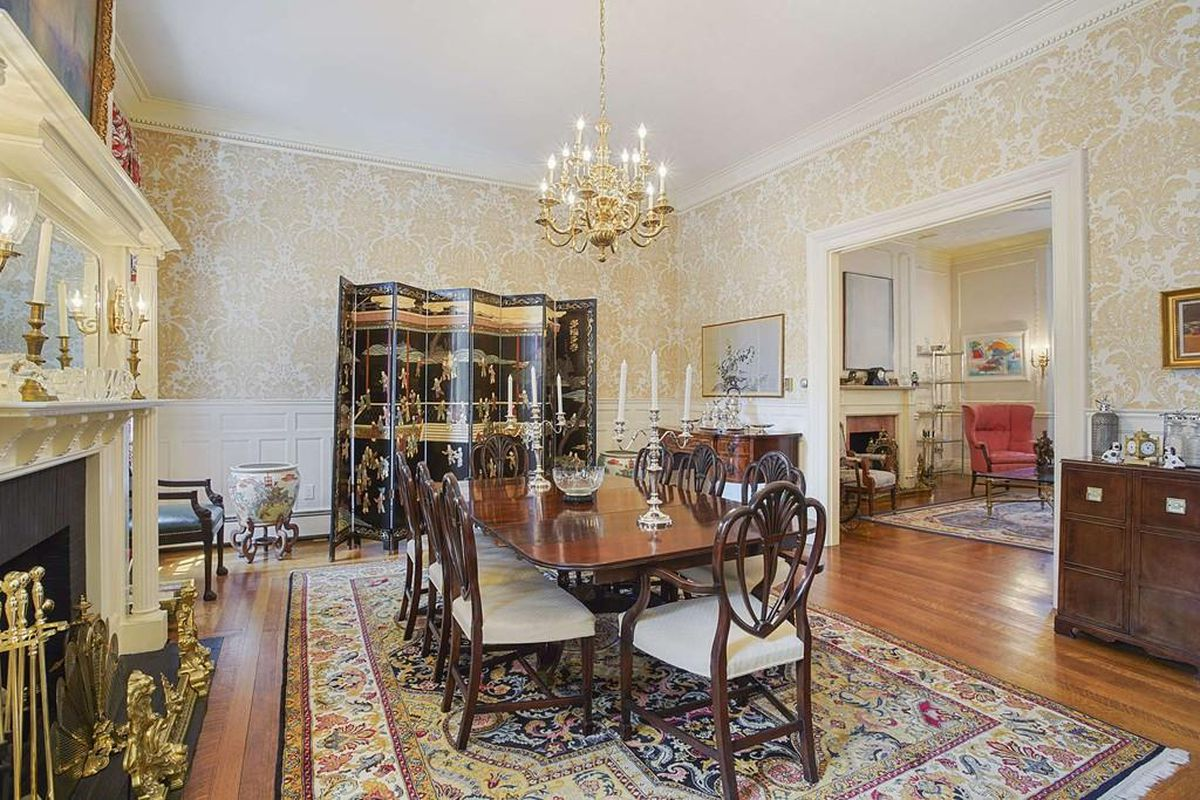 An ornate dining room with a table and chairs and a large opening leading to a living room.