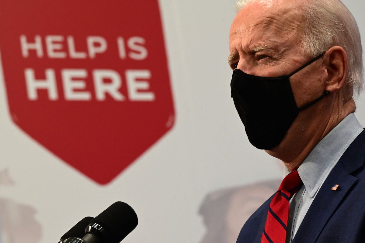 """President Biden in profile in front of a sign that reads, """"Help is here."""""""