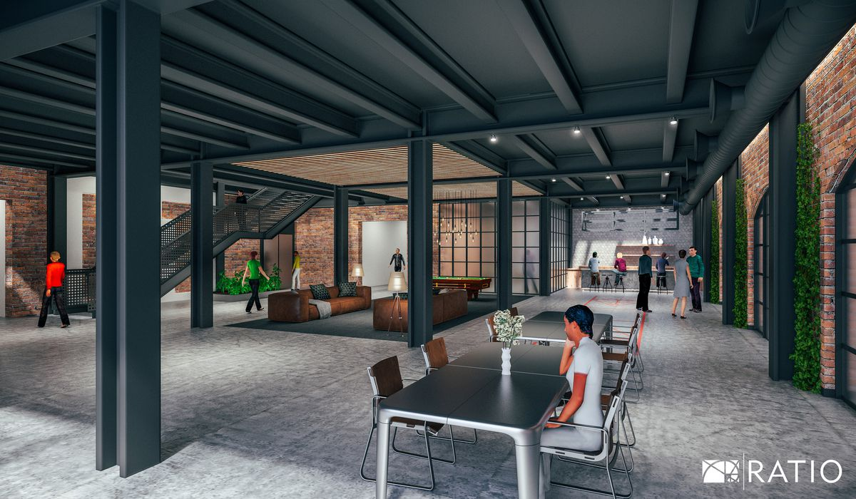 In a low, slung open-layout room, a black iron beam ceiling runs over a concrete floor. There are modern steel tables, a lounge area with brown couches under a skylit, a mesh metal staircase, and a bar in the distance.