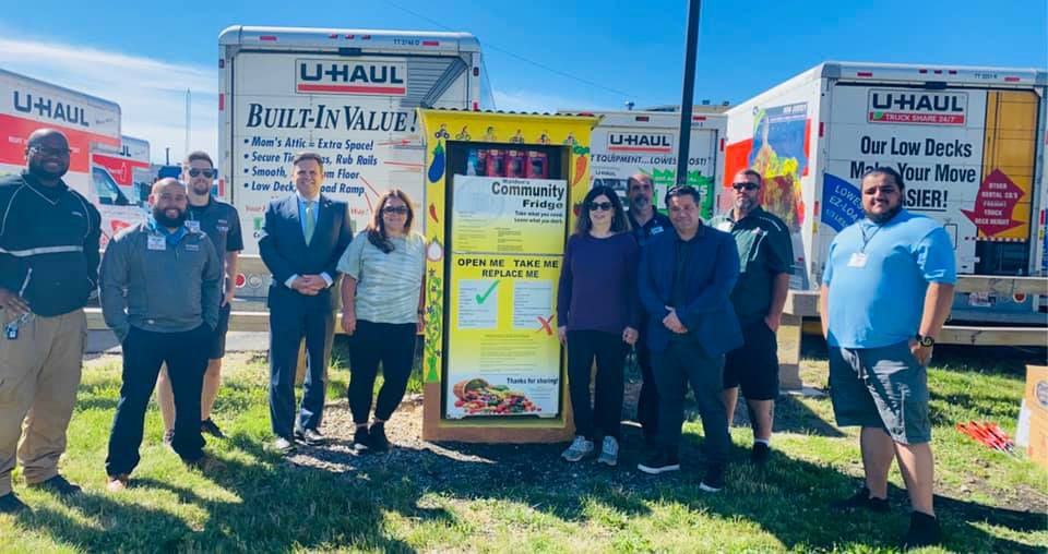 10 people stand around a community fridge, painted yellow in a small yellow pantry, outside in front of several U-Haul trucks