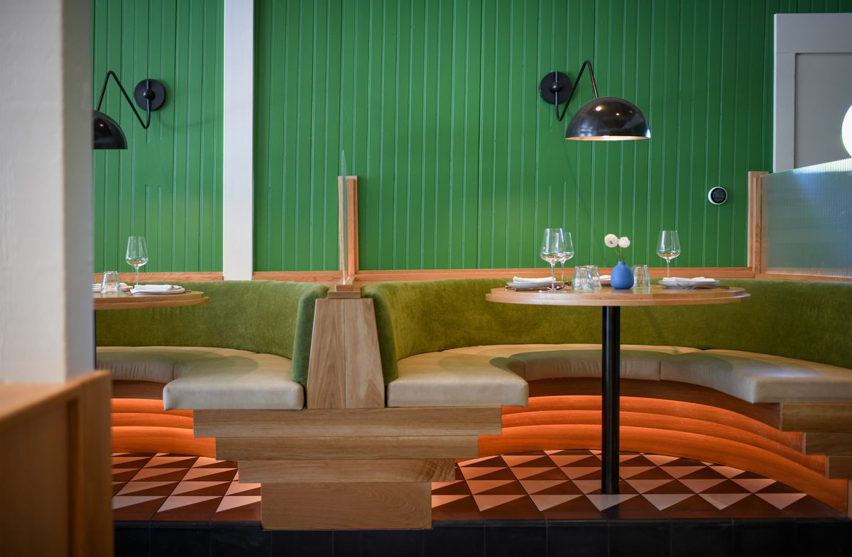 A bright green restaurant with black lamps and light wood booths.