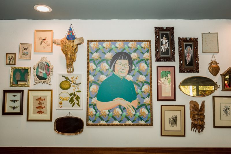 A gallery wall of artwork with a large portrait of a woman at the center
