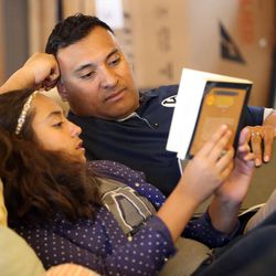Kalani Sitake reads a book with his daughter Skye at home in Provo on Friday, March 11, 2016.
