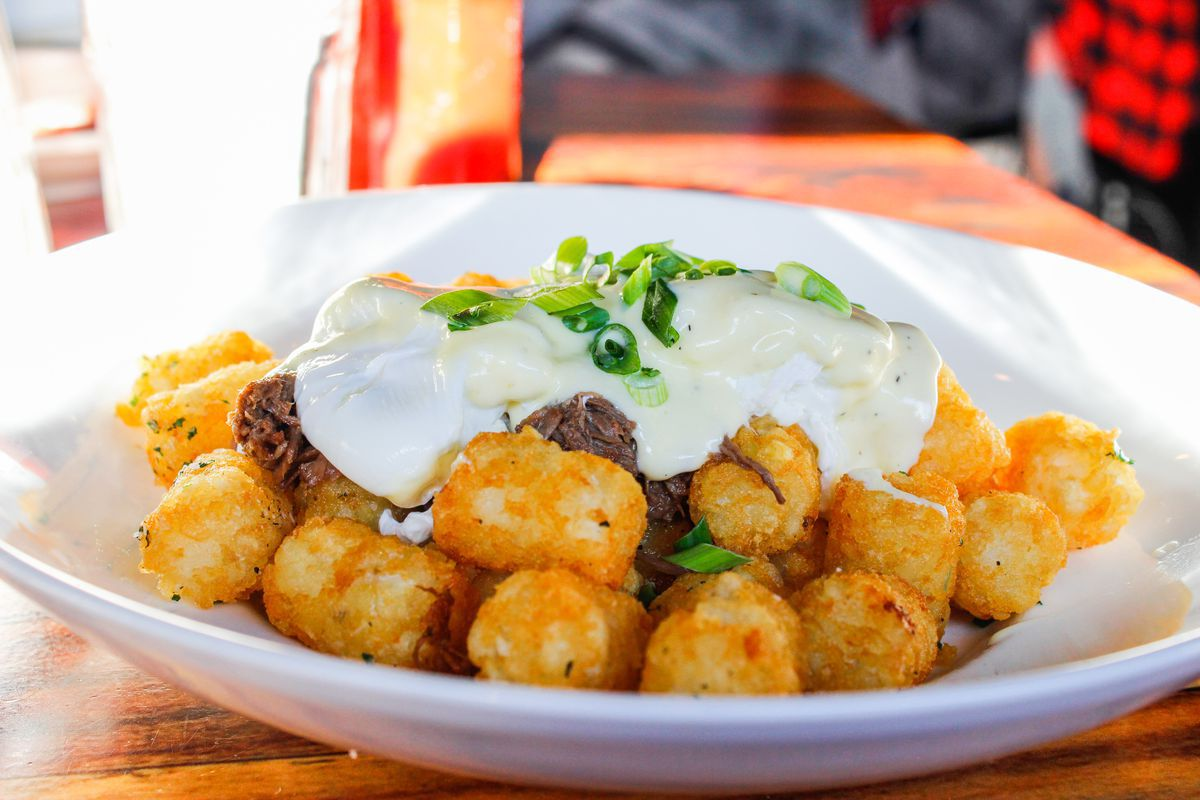 A pile of tater tots sits on a white plate, smothered in braised short ribs, eggs, and scallions