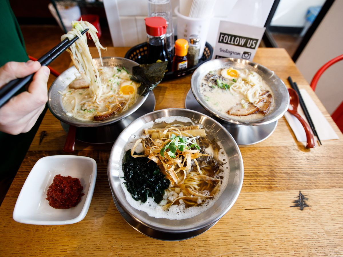 Three bowls of ramen on a wooden table with a woman's hands holding black chopsticks that are pulling up ramen noodles.