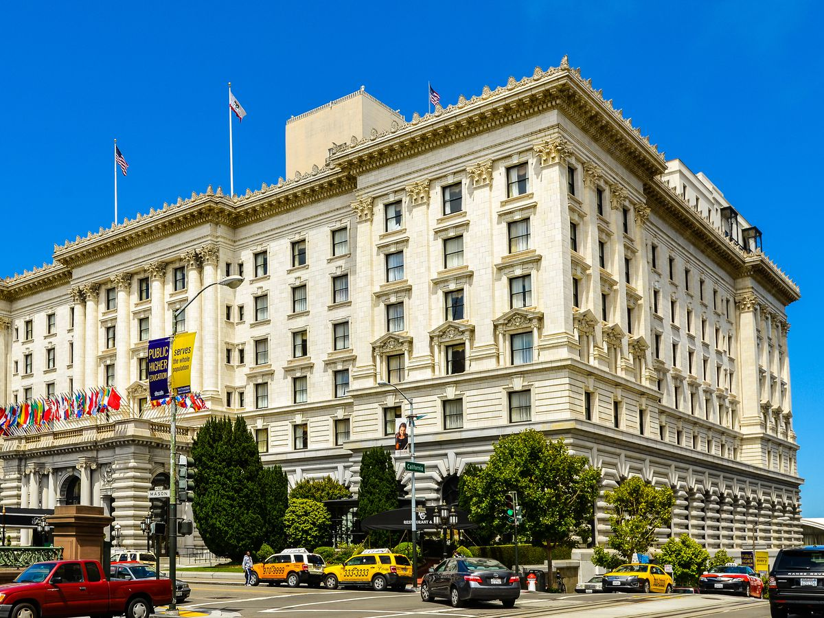 The exterior of a hotel in San Francisco. The facade is white with multiple windows and trees in front.