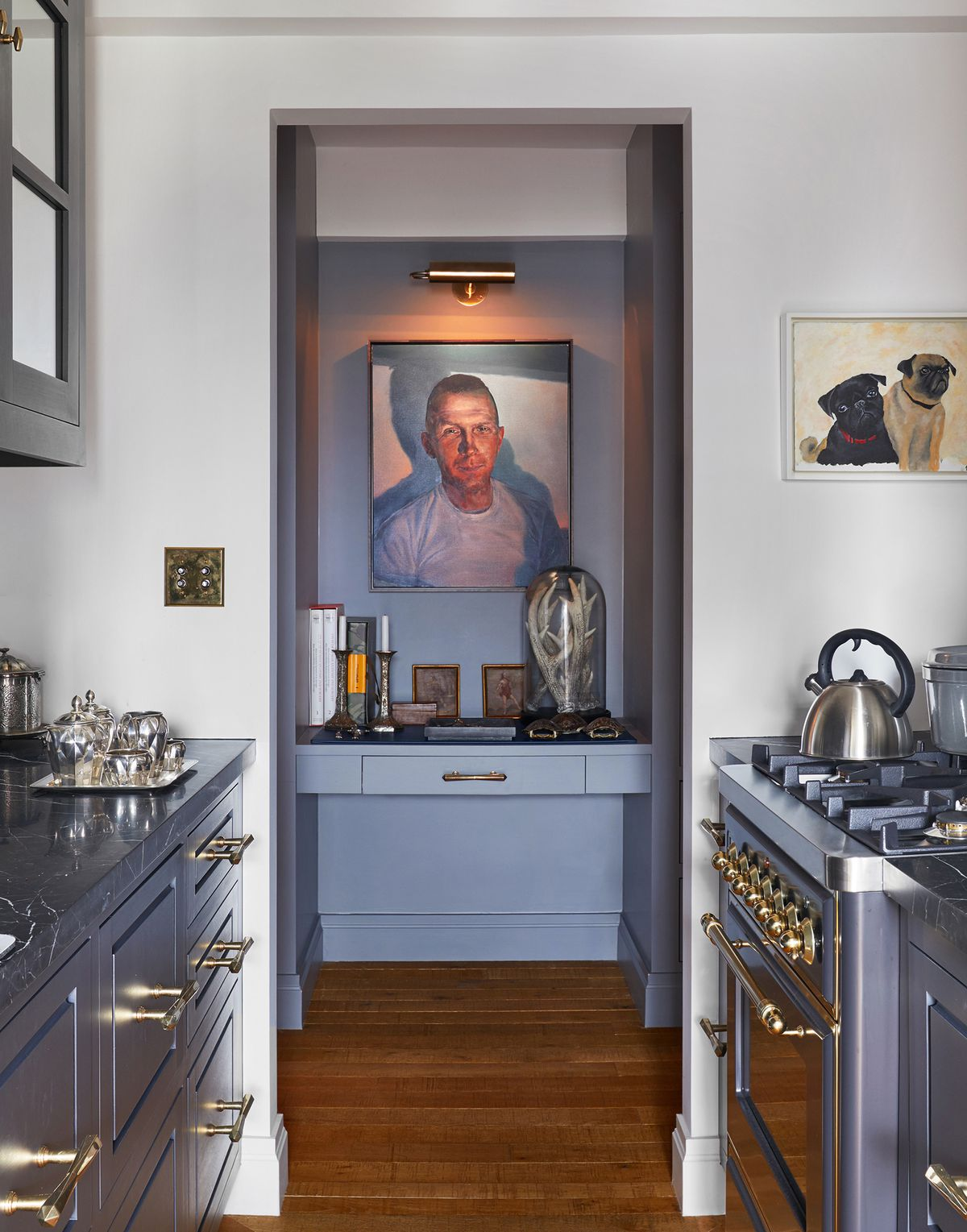 The narrow galley kitchen has gray cabinets and a gray range. Through it, you can see a portrait of Campbell painted by his friend.