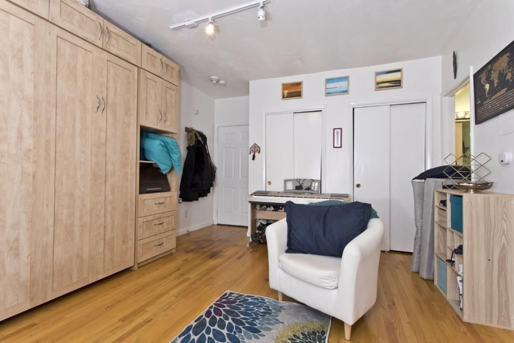 The entry area of a small studio, with a large cabinet and one chair.