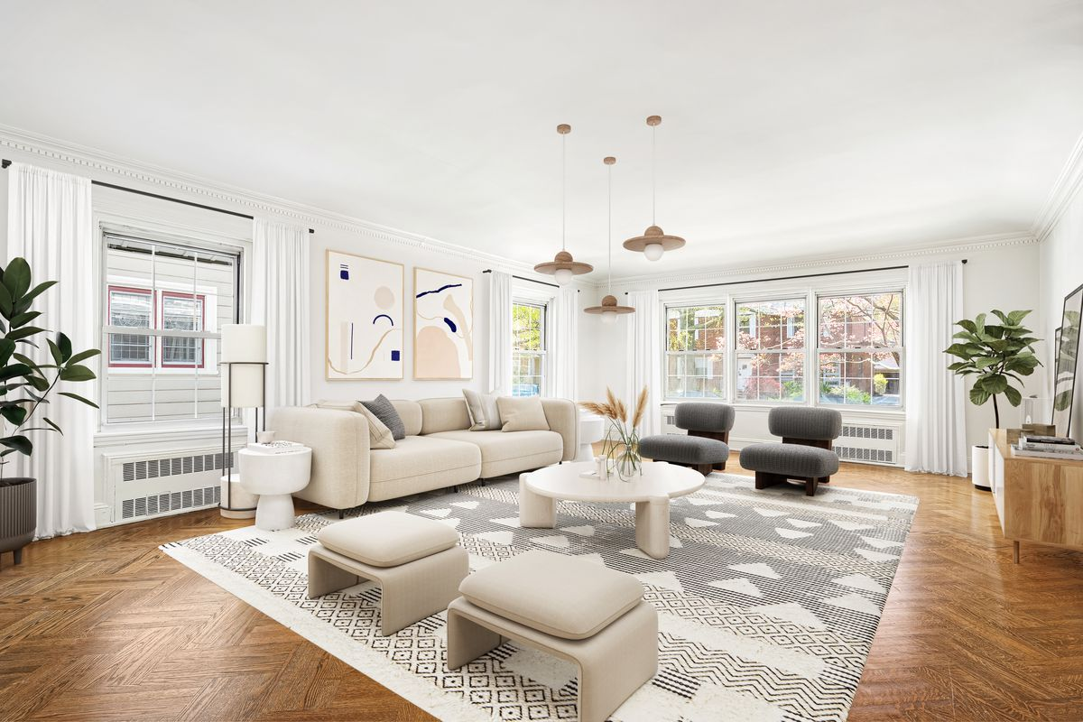 A living area with several windows, hardwood floors, two planters, a round coffee table, and a beige couch.