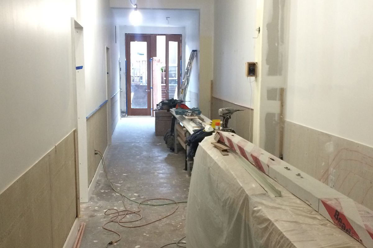 This hallway leading to the backyard will have seating along the right wall.