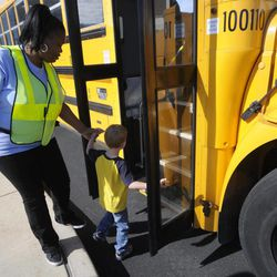 In this photo taken Aug. 18, 2012, Dorcinica Riley, left, a bus monitor in the district, helps a child onto a bus during an open house for parents and students riding the bus for the first time this school year, at the Buffalo Academy for Visual and Performing Arts, in Buffalo, N.Y. The cell phone video of a bus monitor's cruel taunting, in June, ignited a global outpouring of support for the monitor and revulsion at her middle-school tormentors. The video raised questions about the role of bus monitors, including how much they can really do to protect against bullies while seeing riders safely on and off the bus, and how its victim, the authority figure on the bus, could command so little respect.