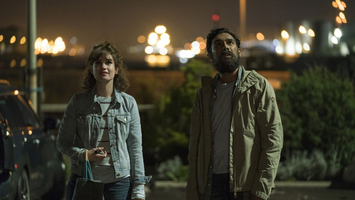 a white woman and an Indian man outside at night looking upward