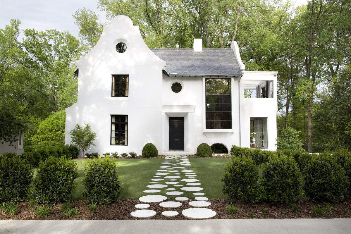 The white, stucco house has a distinct Caribbean style; there's a arched roofline, a large trellised balcony, and circular windows.