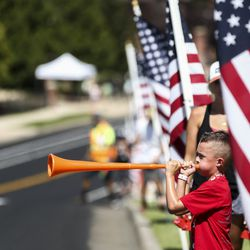 A child blows a horn in support of riders during Stage 3 of the Tour of Utah at Eaglewood Golf Course in North Salt Lake on Thursday, Aug. 15, 2019.