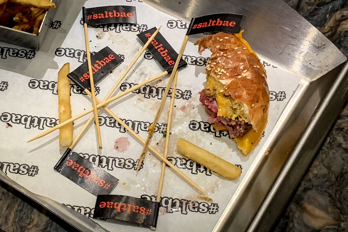 A collection of Salt Bae toothpicks with black and red flags on top sit near the half-eaten remains of a burger