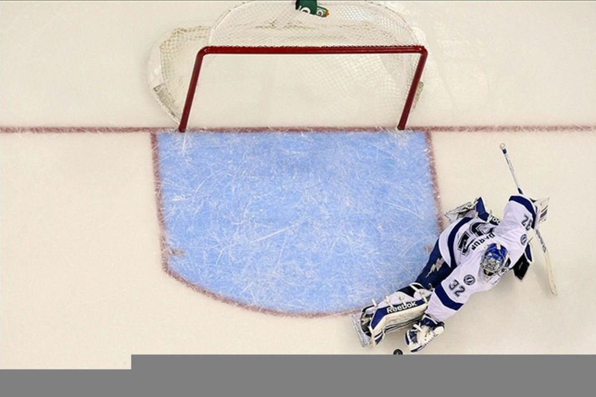 March 3, 2012; Raleigh, NC, USA; Tampa Bay Lightning goalie Mathieu Garon (32) makes a glove save against the Carolina Hurricanes at the RBC center. The Lightning defeated the Hurricanes in overtime, 4-3. Mandatory Credit: James Guillory-US PRESSWIRE