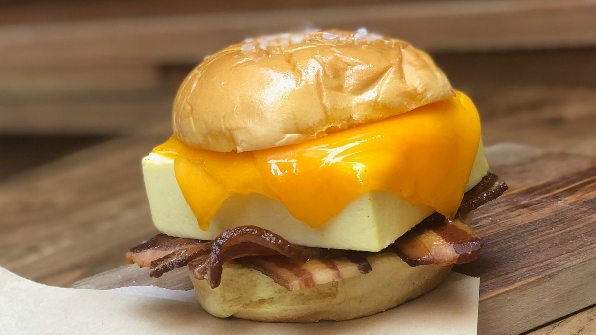 A breakfast sandwich on a bun with melted cheddar, a square egg, and bacon