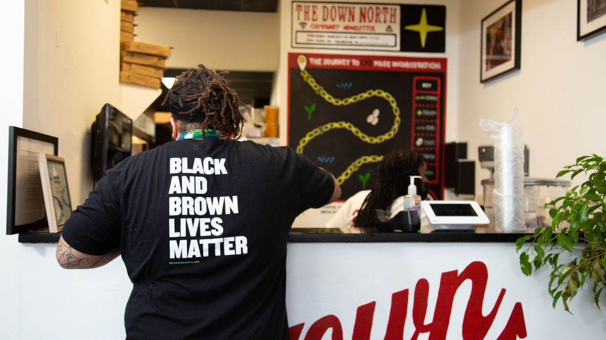 a man with a shirt that says black and brwon lives matter in front of a counter at pizza shop down north