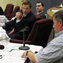 Kansas Secretary of State Kris Kobach, center, questions Joe Montgomery, lower right, a Manhattan, Kan., resident, during a meeting of the State Objections Board, Thursday, Sept. 13, 2012, in Topeka, Kan. The board includes Kobach and, behind him, Attorney General Derek Schmidt and is reviewing Montgomery's objection to the state listing President Barack Obama on its November election ballot.