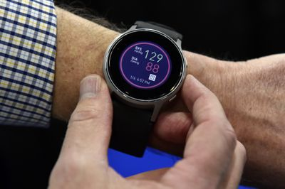 A watch displaying blood pressure reading on a person's wrist.