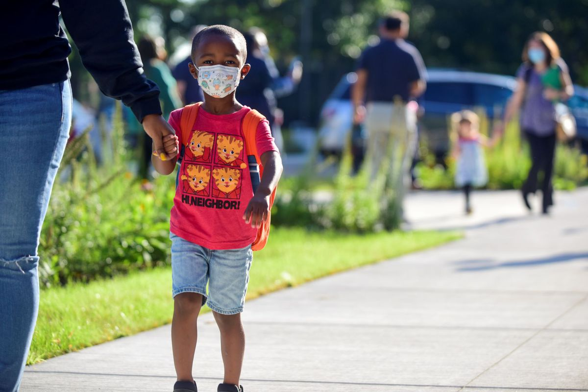 A little boy wearing a red shirt and protective mask holds someone's hand as other children walk behind them on a sidewalk.