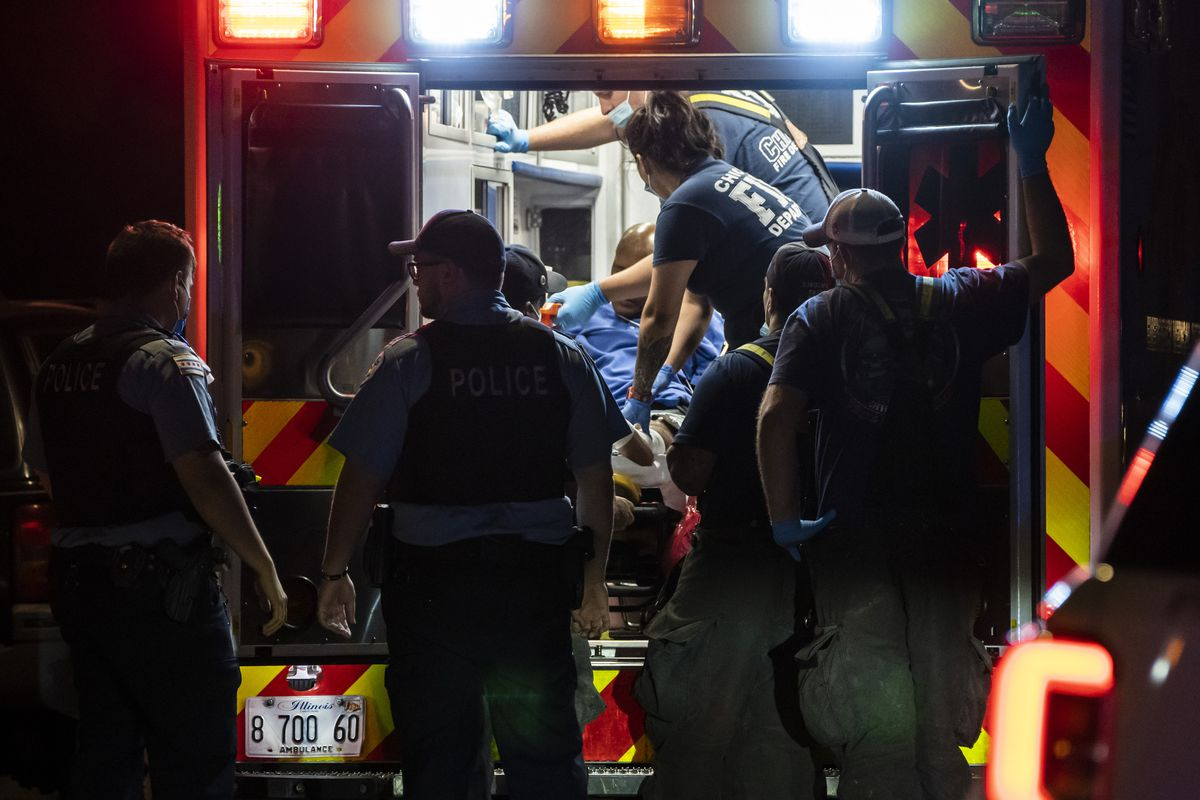 Chicago Fire Department paramedics treat a man who was shot in the leg early Monday outside a home in the 9900 block of South La Salle Street in Fernwood on the South Side.