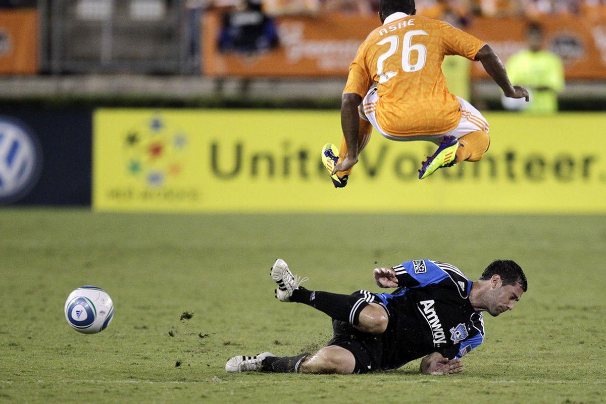 HOUSTON - SEPTEMBER 17:  Corey Ashe #26 of the Houston Dynamo leaps over a sliding Joey Gjertsen #17 of the San Jose Earthquakes at Robertson Stadium on September 17, 2011 in Houston, Texas. Houston won 2-1.  (Photo by Bob Levey/Getty Images)