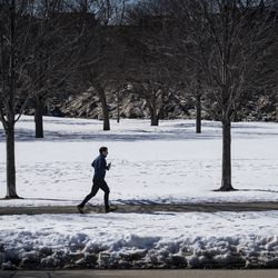 A person jogs near the lakefront near a portion West Montrose Avenue east of Lake Shore Drive that had been closed since March amid fears of the coronavirus pandemic, Tuesday, Feb. 23, 2021. The Chicago Park District announced plans Tuesday to gradually reopen the city's lakefront, playgrounds and indoor swimming pools in response to sustained declines in COVID-19 positivity rates and cases.