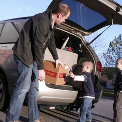 Adam Moore of Taylorsville helps his son load food into  their van. The family delivers meals to homebound seniors.