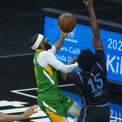Utah Jazz guard Mike Conley, left, drives to the basket as Sacramento Kings center Damian Jones, right, defends during the first quarter of an NBA basketball game in Sacramento, Calif., Sunday, May 16, 2021.