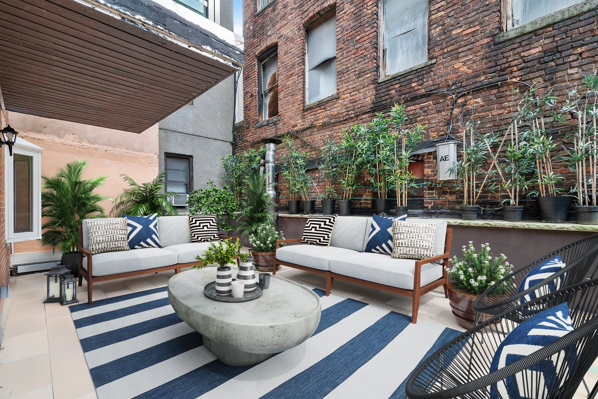 A terrace with a blue and white striped rug, two couches, two chairs, and several planters.