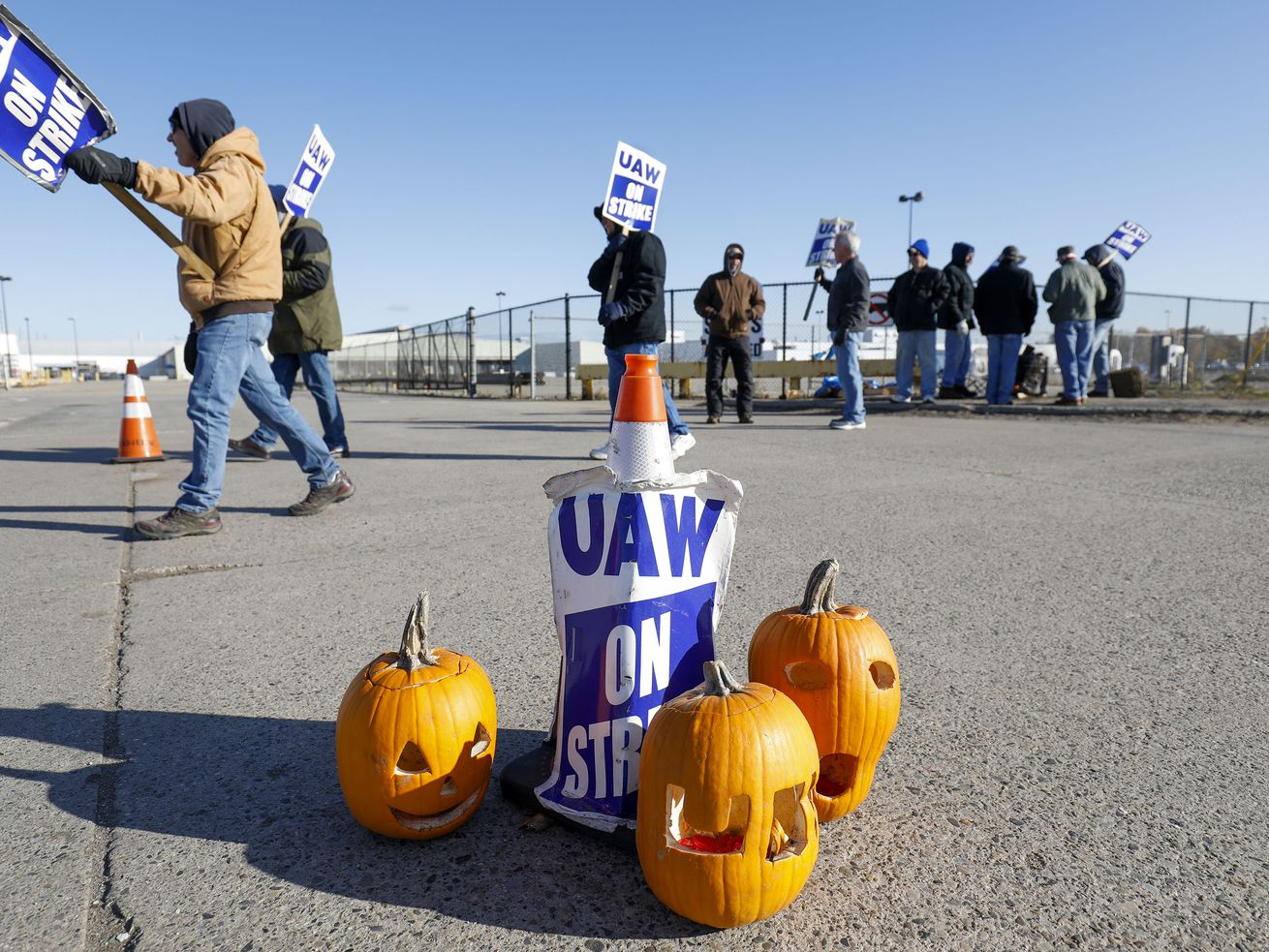 "A picket sign that reads, ""UAW on strike"" sits propped on the ground surrounded by three carved pumpkins. Strikers carrying signs are in the background."