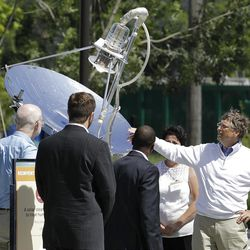 """Bill Gates, right, looks at a device that uses solar energy to treat human waste, as he tours the """"Reinventing the Toliet"""" Fair."""