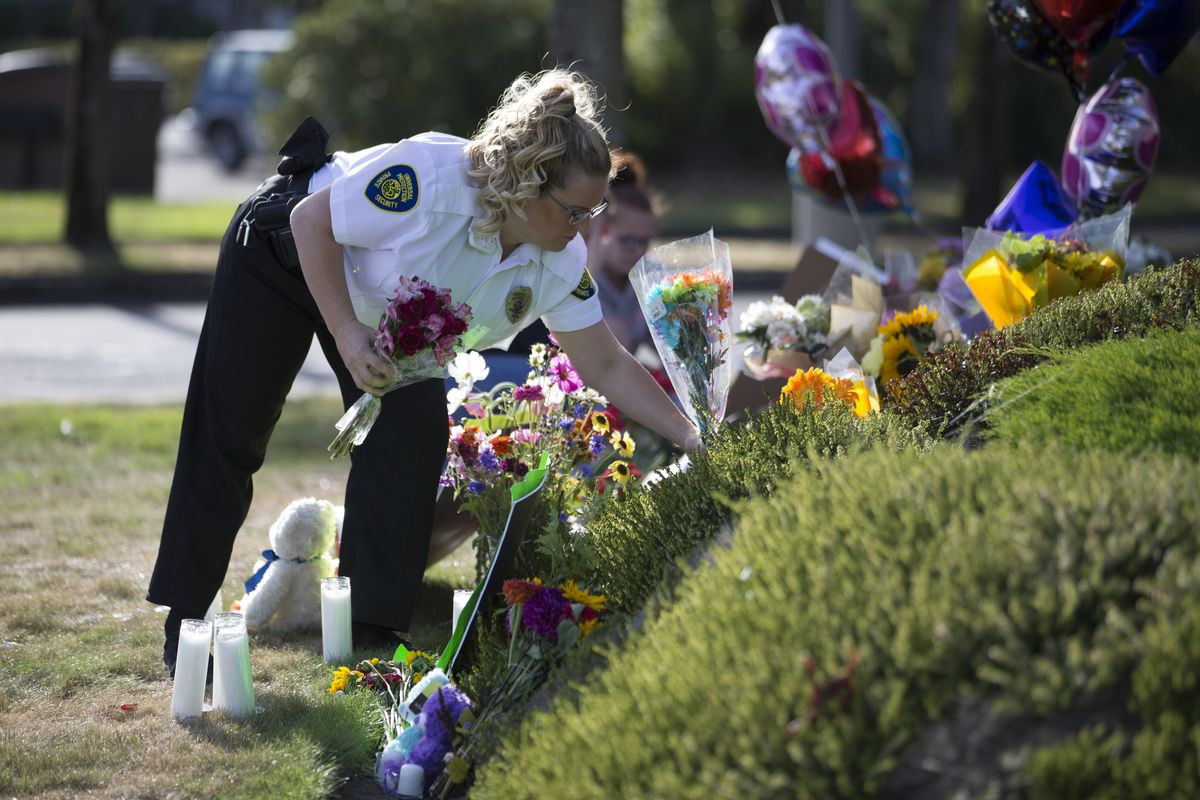 On Sunday in Burlington, Washington, a security guard who works at the Cascade Mall places flowers at a makeshift memorial to the five victims killed in a shooting at the mall on Friday. | Stephen Brashear/AP