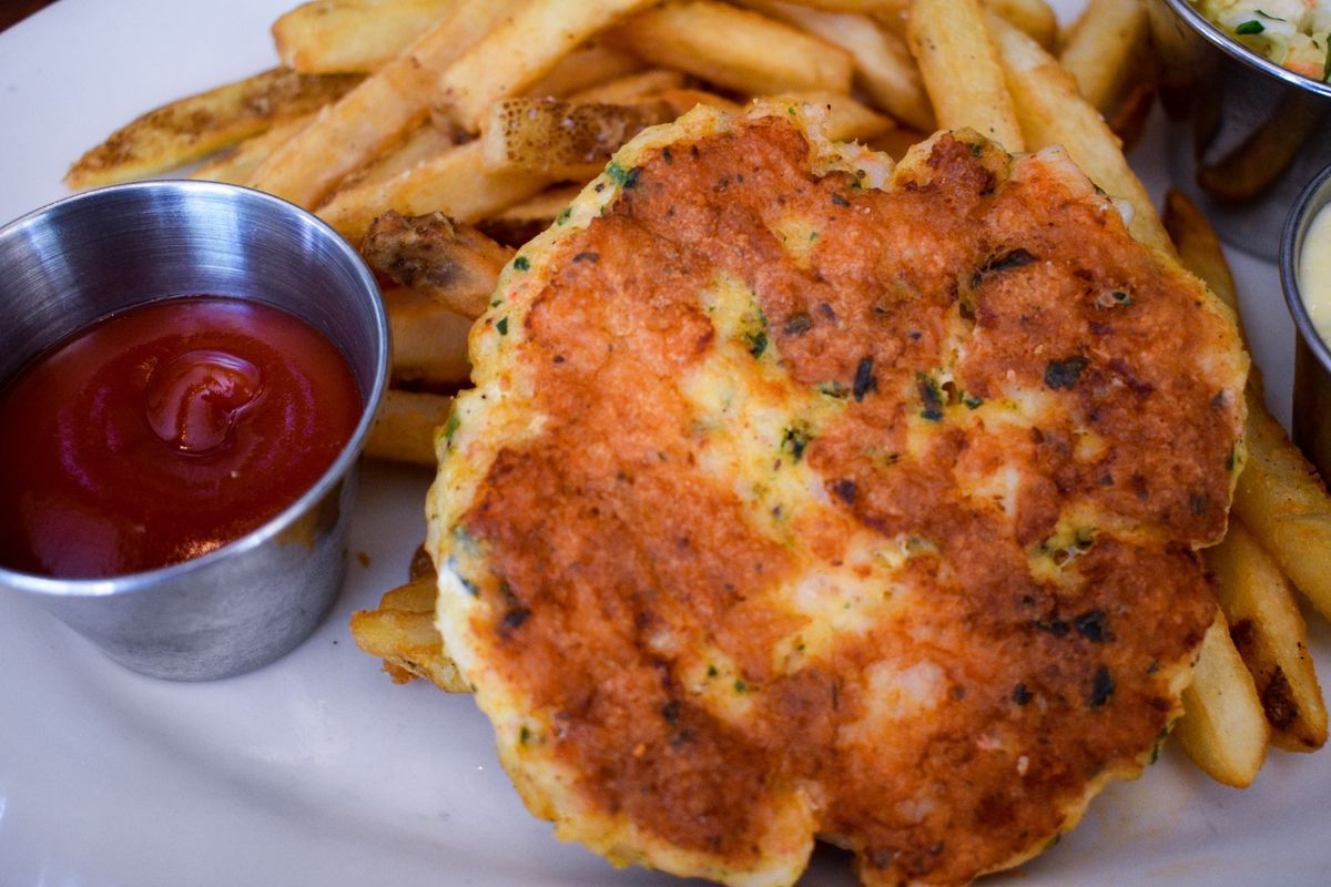 A close-up of a round, browned shrimp cake from Clyde's.
